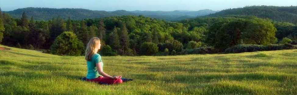 Woman meditating in meadow at Ananda Village