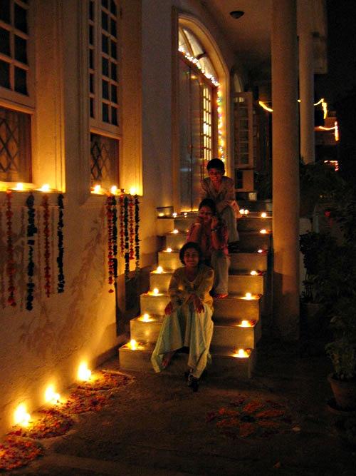Indian devotees Ria, Rahul, and Ayesha sit on steps decorated with Diwali lights, Ananda Ashram, New Delhi.