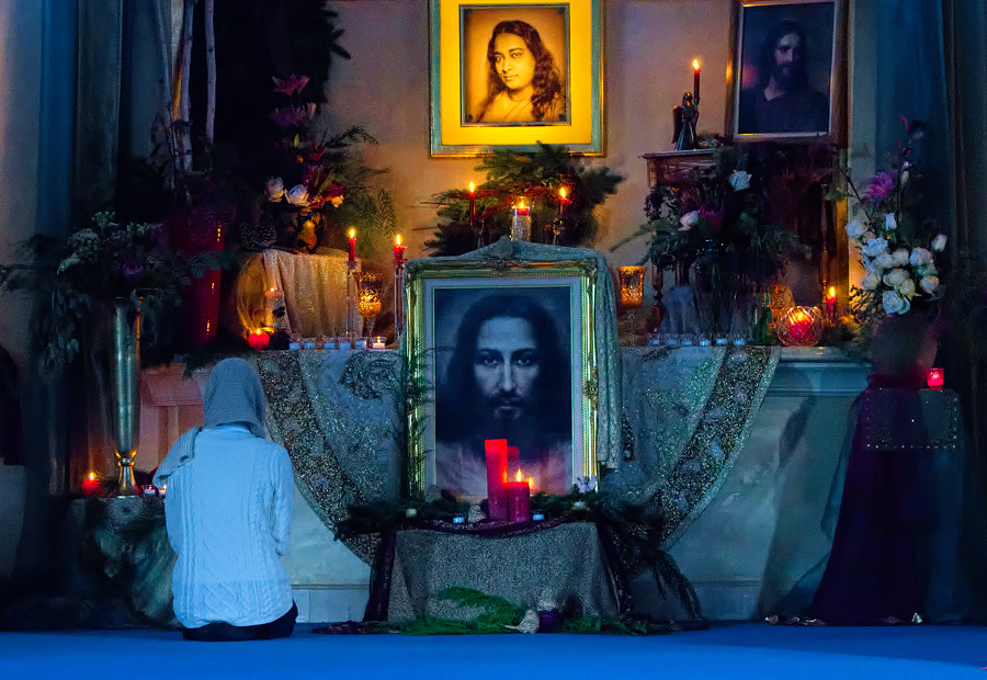 A devotee meditates before a large portrait of Christ.