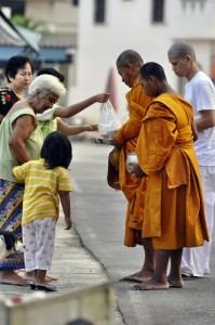 Women give alms to Theravada Buddhist monks in Thailand.