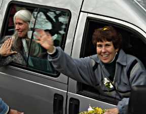 "Shivani (right) waves from the van as the ""Ananda Nine"" return home after eight days in jail."