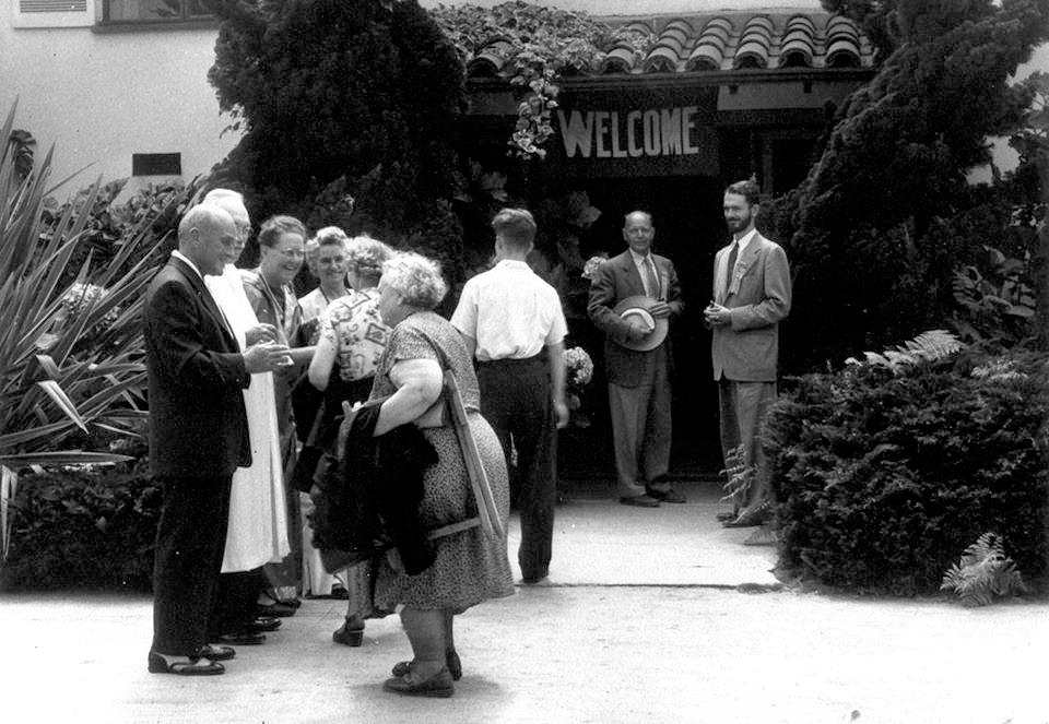As a young monk, Swami Kriyananda, at right, greets visitors at the SRF Hollywood Church..